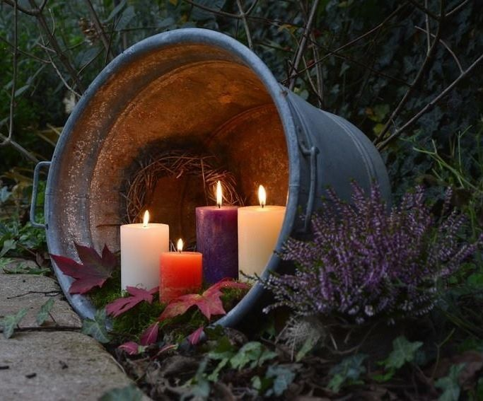 lit candles in a galvanized bucket