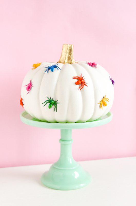 rainbow colored spiders glued on pumpkin